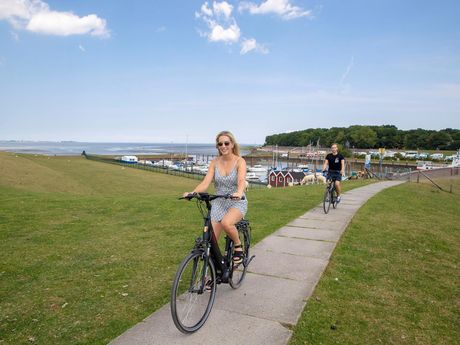 Zwei Fahrradfahrer auf ihren Fahrrädern auf dem Deich von Dangast